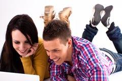 Muchacha y muchacho adolescentes con la computadora portátil blanca Imagen de archivo