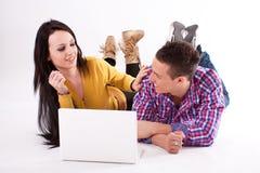 Muchacha y muchacho adolescentes con la computadora portátil blanca Foto de archivo libre de regalías