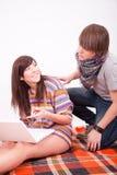 Muchacha y muchacho adolescentes hermosos con el ordenador Fotos de archivo libres de regalías
