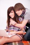 Muchacha y muchacho adolescentes hermosos con el ordenador Foto de archivo libre de regalías