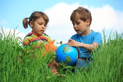 Muchacha y muchacho con el globo en prado Imagenes de archivo