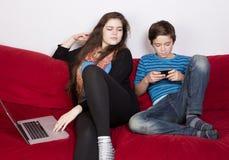 Muchacha y muchacho con el ordenador portátil y el teléfono Imagen de archivo