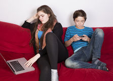 Muchacha y muchacho con el ordenador portátil y el teléfono Fotos de archivo