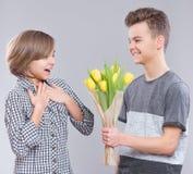 Muchacha y muchacho con las flores Imagen de archivo