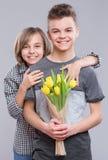 Muchacha y muchacho con las flores Fotos de archivo libres de regalías