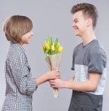 Muchacha y muchacho con las flores Imagen de archivo libre de regalías