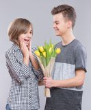 Muchacha y muchacho con las flores Foto de archivo