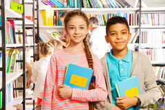Muchacha y muchacho con los libros que se colocan en biblioteca Imágenes de archivo libres de regalías