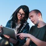 Muchacha y muchacho con PC de la tablilla Fotos de archivo libres de regalías
