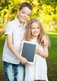 Muchacha y muchacho con PC de la tablilla al aire libre Imagen de archivo