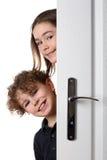 Muchacha y muchacho detrás de la puerta Imagen de archivo libre de regalías