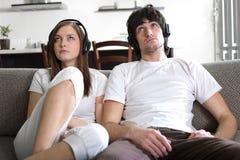Muchacha y muchacho en auriculares Foto de archivo libre de regalías