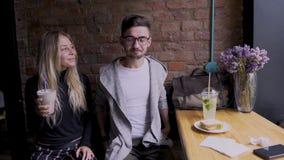Muchacha y muchacho en café La muchacha comparte su cóctel con el individuo almacen de video