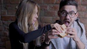 Muchacha y muchacho en café La muchacha toma una tostada de un individuo almacen de metraje de vídeo