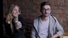 Muchacha y muchacho en café La muchacha toma una tostada de un individuo metrajes