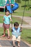 Muchacha y muchacho en el balanceo del parque Imagen de archivo libre de regalías