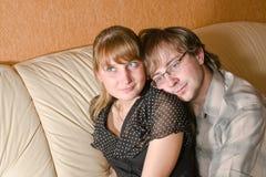 Muchacha y muchacho en el país en el sofá Fotos de archivo