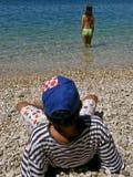 Muchacha y muchacho en la playa de piedra Fotografía de archivo