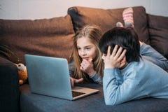 Muchacha y muchacho felices adorables que usa el ordenador portátil y mintiendo en el sofá Imagenes de archivo