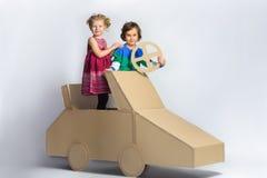 Muchacha y muchacho felices sonrientes cerca del coche de la cartulina Retrato integral Imagen de archivo