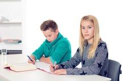 Muchacha y muchacho junto en la sala de clase foto de archivo