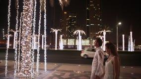 Muchacha y muchacho que caminan en la calle la noche Dubai Entre los árboles de palmas que brillan intensamente metrajes
