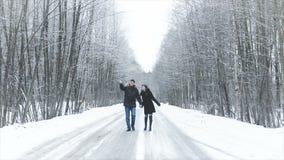 Muchacha y muchacho que caminan a lo largo del camino en el bosque Lleve a cabo las manos Se besan almacen de video