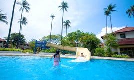 Muchacha y muchacho que disfrutan de la diapositiva por la piscina Foto de archivo libre de regalías