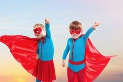 Muchacha y muchacho que fingen ser super héroe fotografía de archivo libre de regalías