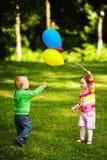 Muchacha y muchacho que juegan con los globos en parque Imagen de archivo libre de regalías