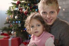Muchacha y muchacho que juegan en el cuarto con un árbol de navidad Foto de archivo libre de regalías