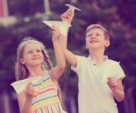 Muchacha y muchacho que juegan los aviones de papel Fotos de archivo