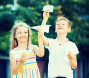 Muchacha y muchacho que juegan los aviones de papel Foto de archivo libre de regalías