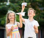 Muchacha y muchacho que juegan los aviones de papel Imágenes de archivo libres de regalías