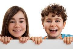 Muchacha y muchacho que llevan a cabo a la tarjeta en blanco Imagen de archivo libre de regalías