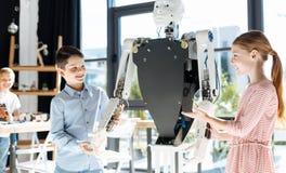 Muchacha y muchacho que llevan a cabo las manos de un robot humano grande Foto de archivo libre de regalías