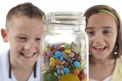 Muchacha y muchacho que miran el tarro dulce Foto de archivo libre de regalías