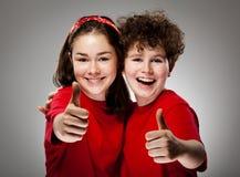 Muchacha y muchacho que muestran la muestra aceptable Fotografía de archivo libre de regalías
