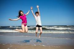 Muchacha y muchacho que saltan en la playa Imagen de archivo