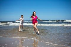 Muchacha y muchacho que saltan en la playa Imagen de archivo libre de regalías