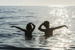 Muchacha y muchacho que se bañan y que bailan en el mar en verano Foto de archivo