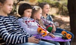 Muchacha y muchacho que se sientan en el parque en un banco en primavera Imagenes de archivo