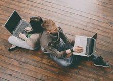 Muchacha y muchacho que usa los ordenadores portátiles que se sientan y que estudian en un piso Foto de archivo libre de regalías