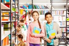 Muchacha y muchacho sonrientes en biblioteca con los libros Imagen de archivo