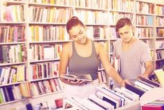 Muchacha y muchacho sonrientes que toman los nuevos libros Imagen de archivo libre de regalías