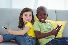 Muchacha y muchacho sonrientes que usa los teléfonos móviles Imagen de archivo libre de regalías