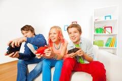 Muchacha y muchachos con las palancas de mando que juegan la videoconsola Foto de archivo