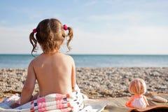 Muchacha y muñeca en la playa Fotos de archivo libres de regalías