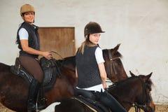 Muchacha y mujer joven en arena interior del montar a caballo Imagenes de archivo