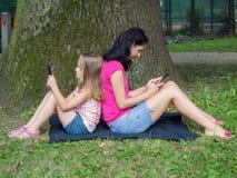 Muchacha y mujer joven que usa la tableta imagen de archivo libre de regalías
